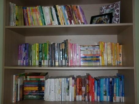 meletakkan koleksi buku di rak secara berjajar